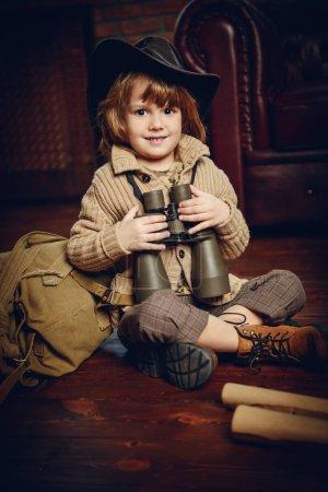 Photo pour Garçon souriant jouant à la maison dans voyageur. Enfance. Fantaisie, imagination . - image libre de droit