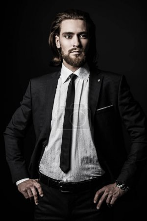 Photo for Fashion shot. Handsome young man posing in elegant suit and white shirt over black background. Men's beauty, fashion. - Royalty Free Image