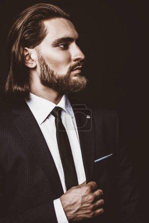 Photo pour Mode prise de vue. Beau jeune homme posant en costume élégant et chemise blanche sur fond noir. Beauté masculine, mode. - image libre de droit