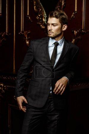 Foto de Imponer bien vestidas a hombre un apartamentos de lujo con interiores clásicos. Lujo. Belleza de los hombres, moda. - Imagen libre de derechos