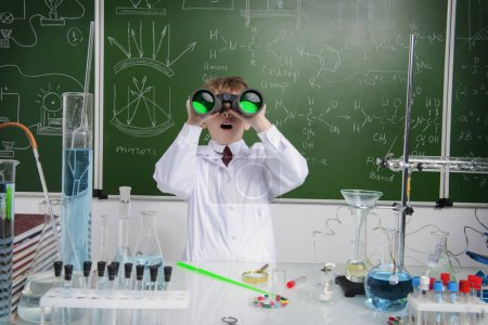 Photo for Schoolboy looks through binoculars by a chalkboard on a chemistry lesson. Educational concept. - Royalty Free Image