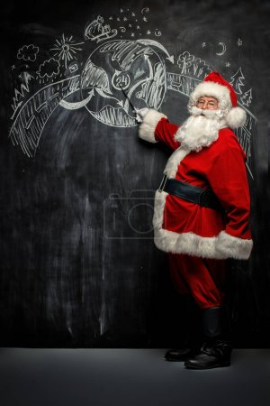 Photo for Full length portrait of Santa Claus standing in a classroom near the blackboard. Merry Christmas and Happy New Year! - Royalty Free Image