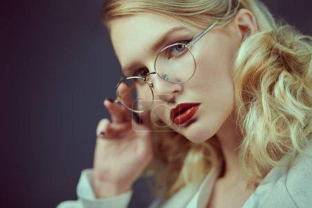 Photo pour Portrait studio d'une femme blonde à la mode dans des lunettes élégantes. Optique, lunettes. Espace de copie . - image libre de droit