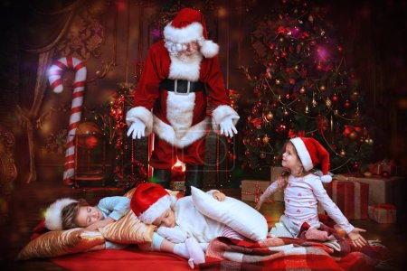 Photo for Santa Claus is putting gifts while children are sleeping at home. Merry Christmas and Happy New Year. Miracle time. - Royalty Free Image