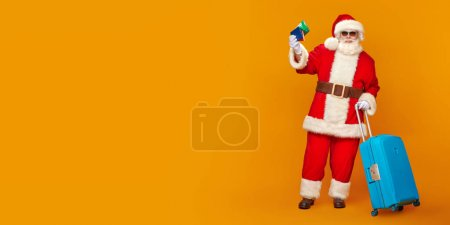 Photo for Santa Claus goes on vacation. Christmas Holidays, tourist trips to hot tropical countries. Bright yellow background. Copy space. - Royalty Free Image