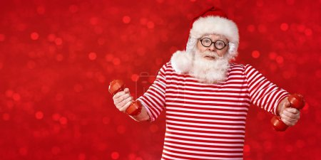 Photo for Funny Santa Claus doing exercises with dumbbells on a festive sparkling red background. Sport and healthy lifestyle. Copy space. - Royalty Free Image