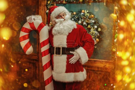 Photo for Santa Claus is standing in a beautiful New Year's interior with a giant candy. Merry Christmas and Happy New Year! - Royalty Free Image