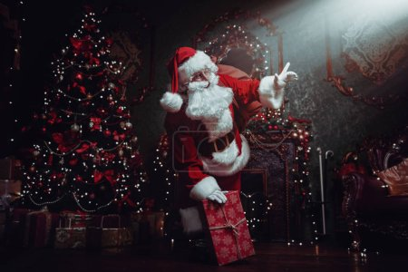 Photo for Santa Claus brought gifts for Christmas. He stands in a night room  with beautiful Christmas tree and fireplace. Christmas and New Year concept. - Royalty Free Image