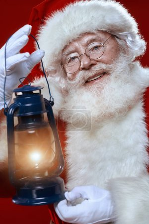 Photo for Close-up portrait of a jolly Santa with a glowing lantern over festive red background. Merry Christmas and Happy New Year! - Royalty Free Image