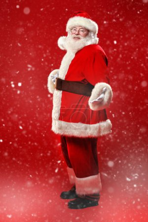 Photo for Full length portrait of the good old Santa Claus under a snowfall on a red background. Merry Christmas and Happy New Year! Copy space. - Royalty Free Image
