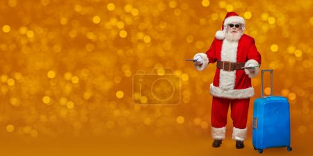 Photo for Portrait of perplexed Santa in sunglasses with documents and suitcase on a golden shining background. Merry Christmas and Happy New Year! Copy space. - Royalty Free Image