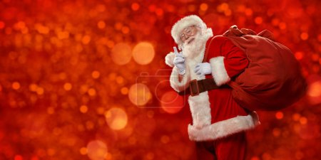 Photo for Good old Santa Claus with a bag of gifts shakes his finger under a snowfall on a red shimmering background. Merry Christmas and Happy New Year! Copy space. - Royalty Free Image