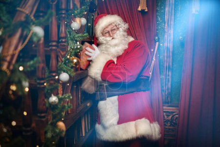 Photo for Fairy tales on Christmas. Jolly Santa Claus takes fairy tales from a bookshelf in a house beautifully decorated for Christmas. - Royalty Free Image