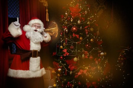 Photo for Jolly Santa Claus sneaked into the house and listens. Christmas and New Year concept. - Royalty Free Image