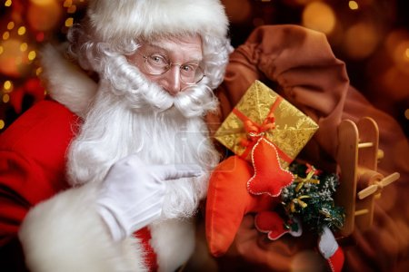 Photo for Magical Christmas time. Close-up portrait of a jolly Santa Claus with gifts. Magic golden lights sparkle around. Christmas and New Year concept. - Royalty Free Image