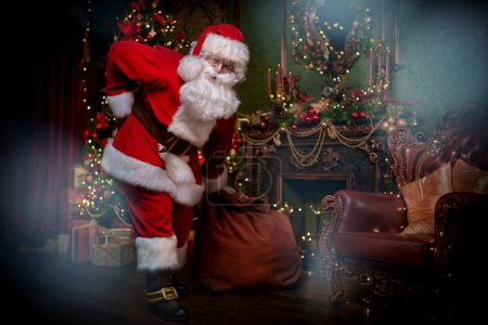 Photo for Santa Claus is getting out of the fireplace with a bag of gifts. Beautiful Christmas interior. Christmas and New Year concept. - Royalty Free Image