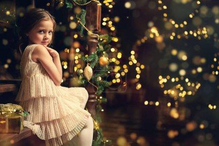 Photo pour Fille Cute en belle robe de fête est assise sur les escaliers décorés pour Noël. Noel et Nouvel An. - image libre de droit