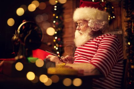 Photo for Santa Claus is preparing for Christmas at his wooden home - he sews gifts on a sewing machine. Santa Claus workshop. Christmas decoration. - Royalty Free Image