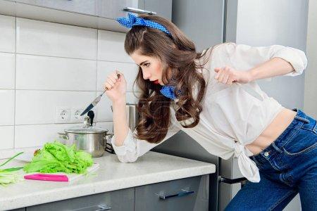 """Photo pour """"Diet and weight loss concept"""". Une jeune jolie femme expressive prépare une salade diététique dans sa cuisine. Style de ramassage. - image libre de droit"""