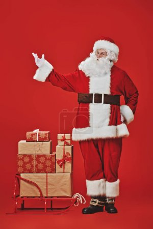 Photo for Full length portrait of the good old Santa Claus carrying gifts on a sleigh under a snowfall on a red background. Delivery service of Santa Claus. - Royalty Free Image