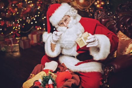 Photo for Santa Claus takes the gifts out of the bag. Christmas and New Year concept. Home decoration. - Royalty Free Image