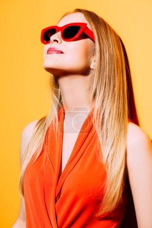 Photo pour Un portrait d'une jeune dame gaie posant dans des lunettes de soleil au-dessus du fond jaune. Été, beauté. - image libre de droit