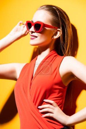 Foto de Retrato de una joven alegre posando con gafas de sol sobre el fondo amarillo. Verano, belleza . - Imagen libre de derechos