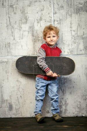 Photo pour Portrait complet d'un jeune écolier heureux posant en studio sur fond gris avec une planche à roulettes. Enfants mode décontractée, éducation . - image libre de droit