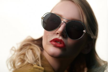Photo for Close-up portrait of a beautiful young woman in modern sunglasses. Optics and eyewear style. - Royalty Free Image