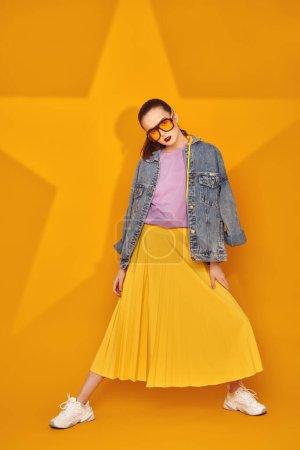 Photo pour Les jeunes modernes ont l'air. Belle jeune fille en vêtements d'été brillants posant sur un fond jaune avec une étoile. Beauté, mode. - image libre de droit