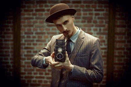 Photo pour Concept rétro. bel homme photographe dans un costume élégant travaille avec son vieil appareil photo sur un fond de mur de briques . - image libre de droit