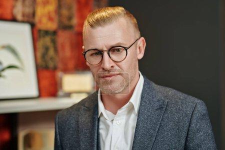 Photo pour Portrait d'un homme d'affaires respectable d'âge moyen en costume et lunettes élégants debout à son bureau. Style commercial. Optique pour les hommes. - image libre de droit