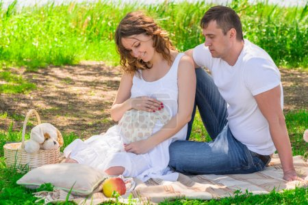 Family in anticipation of a child, rest near a lake in a park on