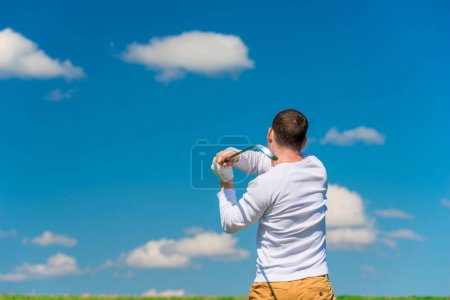 male golfer while hitting the ball view from back to field
