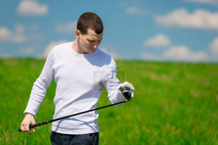 portrait of a golfer inspecting his golf club before playing on