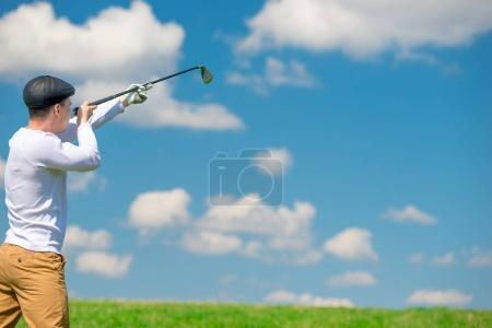 golfer is aiming with a golf club, shooting on the playing field
