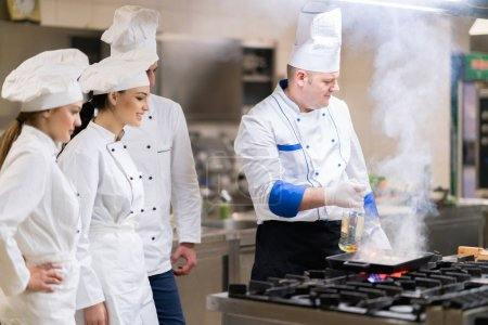 Photo for Chef in restaurant kitchen at stove with pan doing flambe on food - Royalty Free Image
