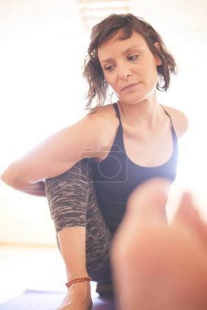 Photo pour Yogi fait de l'exercice assis agrippant le genou avec le bras - image libre de droit