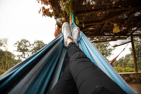 Photo for View of the legs of a young woman on an hammock resting - Royalty Free Image