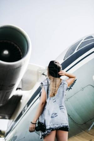 Beautiful tourist woman posing near the plane against jet engine