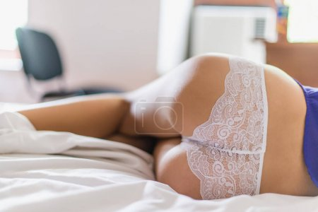 Young sexy woman legs in white lace lingerie on white background. Flat lay of female legs in white lace lingerie. Cropped image of lying young woman sexy body.