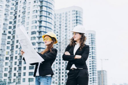 Two business women in protective helmets and safety glasses look