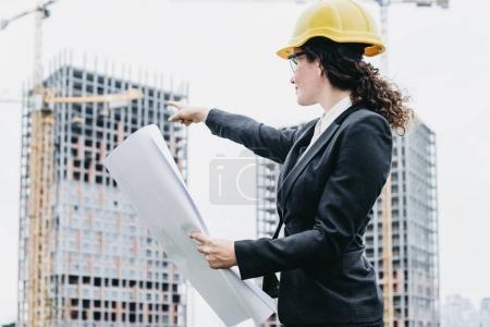 Photo pour Portrait d'une ingénieure regardant la construction. Architecte femme avec un modèle à la main et un casque jaune avec une mise au point sélective. Concept Ingénieur et travail d'entreprise . - image libre de droit