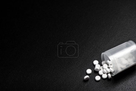 White pills spilling out of a bright pill bottle