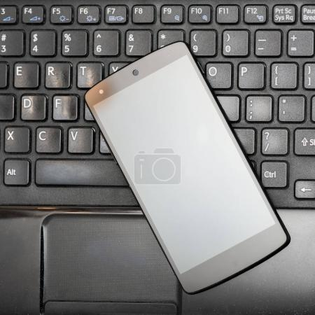 Close look of smartphone on black laptop keyboard