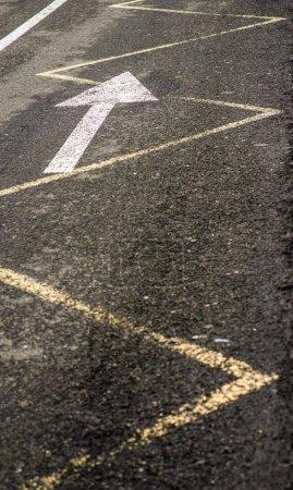 The marks on the asphalt road in the city. Arrow on asphalt
