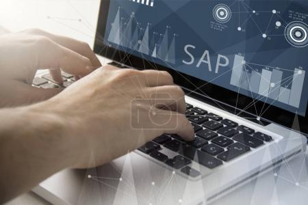 man using a laptop with sap software