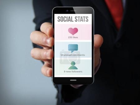 homme d'affaires détenant smartphone avec des statistiques sociales