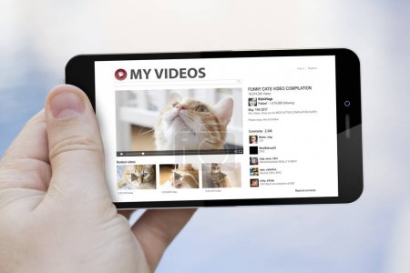 Photo for Mobile video concept: male hand holding smartphone with cats video streaming website on screen - Royalty Free Image