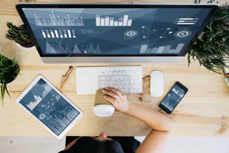 Photo pour Vue aérienne de la femme buvant du café et des appareils montrant des graphiques des données financières - image libre de droit